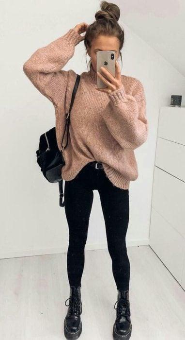 Chica usando suéter holgado color rosa palo, jeans y botines negros