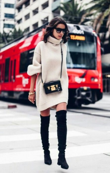 Girl wearing long pearl color baggy sweater, with high black boots
