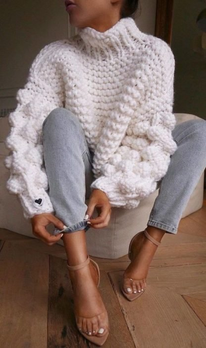 Girl wearing loose white sweater with wide sleeves, jeans and stilettos