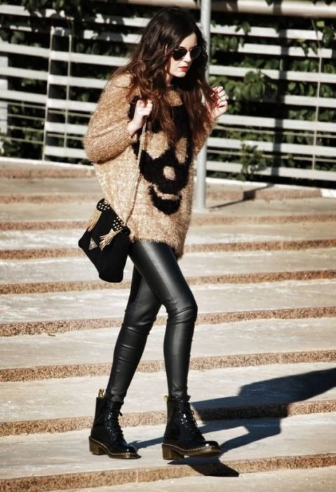 Girl wearing loose beige skull print sweater, leggings and black ankle boots