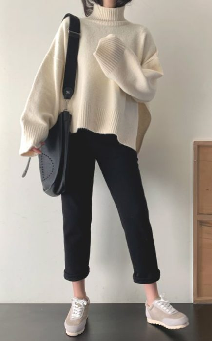 Girl wearing loose pearl-colored sweater, with black straight pants and tennis shoes
