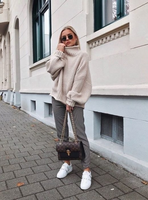 Girl wearing loose beige sweater, with straight pants and tennis shoes