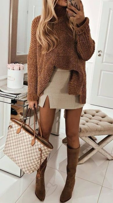 Girl wearing baggy camel sweater and plaid mini skirt with camel boots