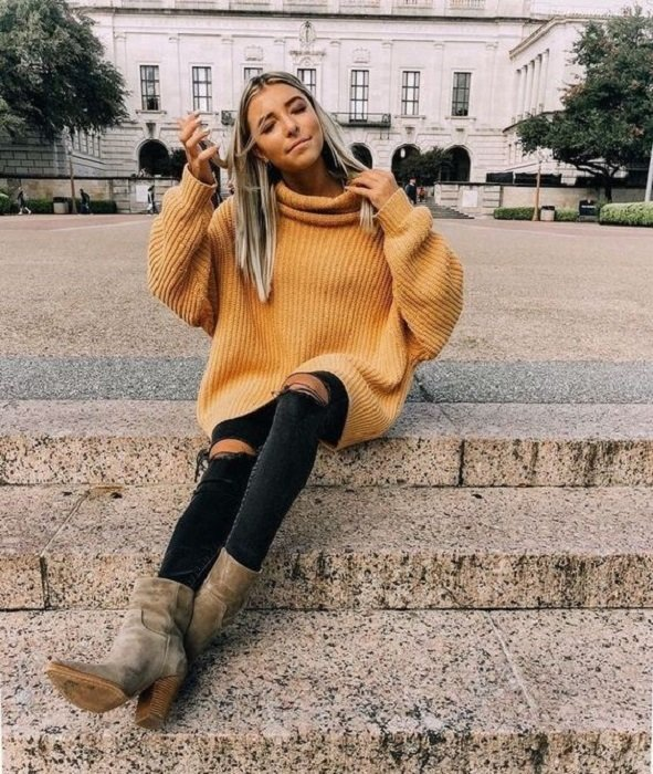 Girl wearing loose mustard sweater, ripped jeans and gray ankle boots