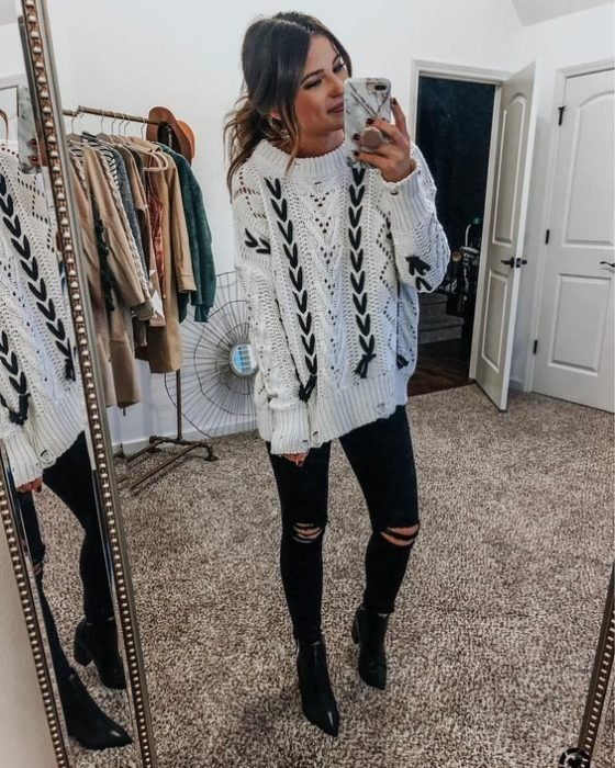 Girl wearing loose white sweater and black details, ripped jeans and high-heeled ankle boots
