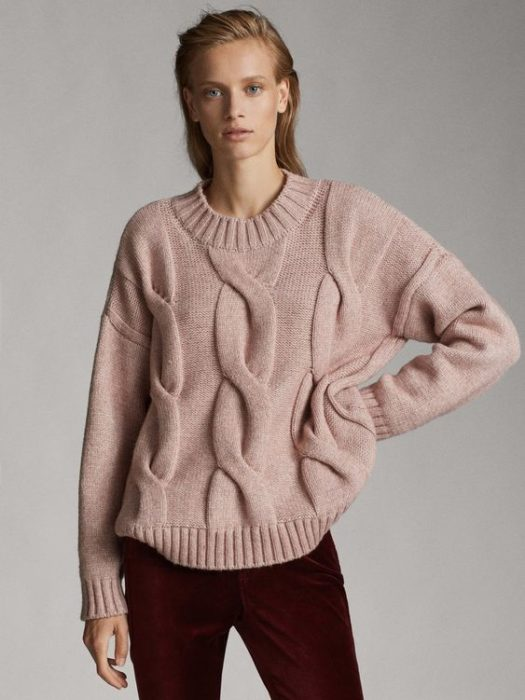 Chcia wearing black jeans and a pale pink sweater