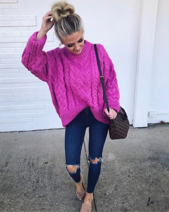 Girl wearing fuchsia loose sweater, ripped jeans and flats