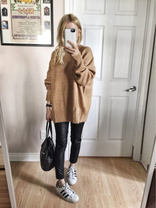 Girl wearing loose camel sweater with black leggings and tennis shoes