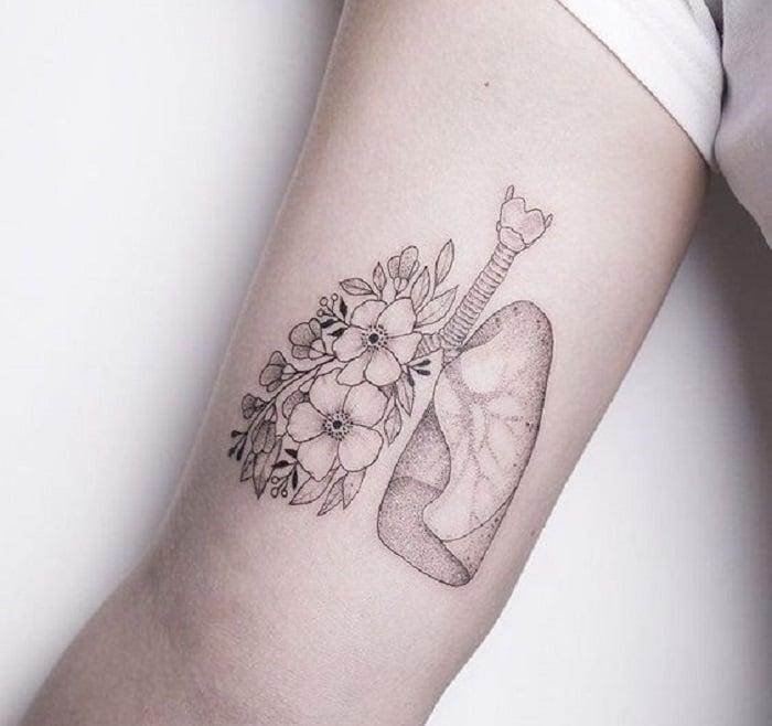 Tatuaje en la parte interna del brazo, de unos pulmones, uno de ellos con flores