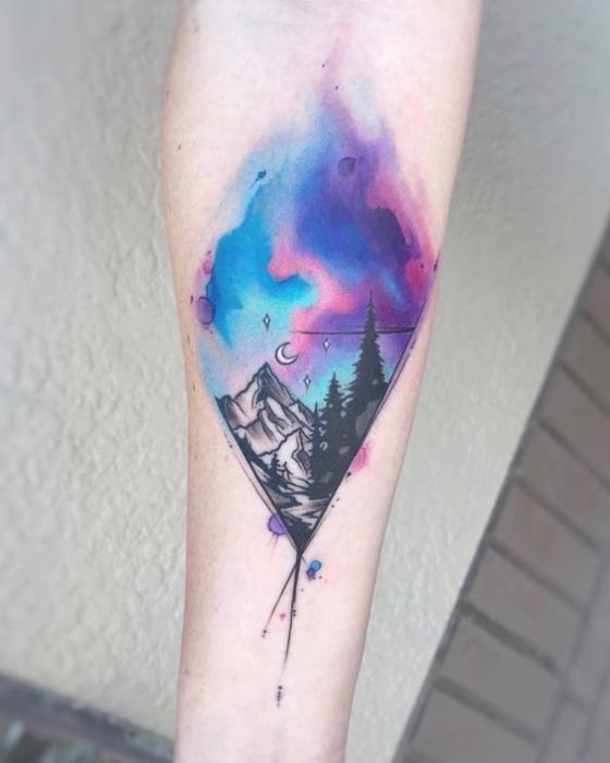 Rhombus tattoo of a mountain and trees with colors of a northern lights