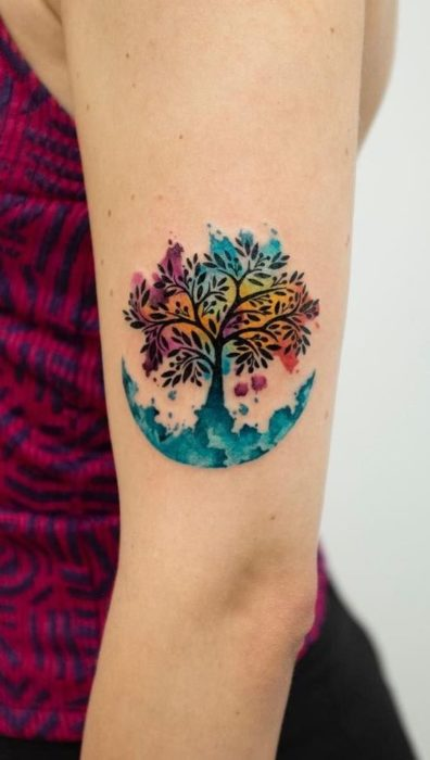 Tree of life tattoo and background of different colors, on the forearm