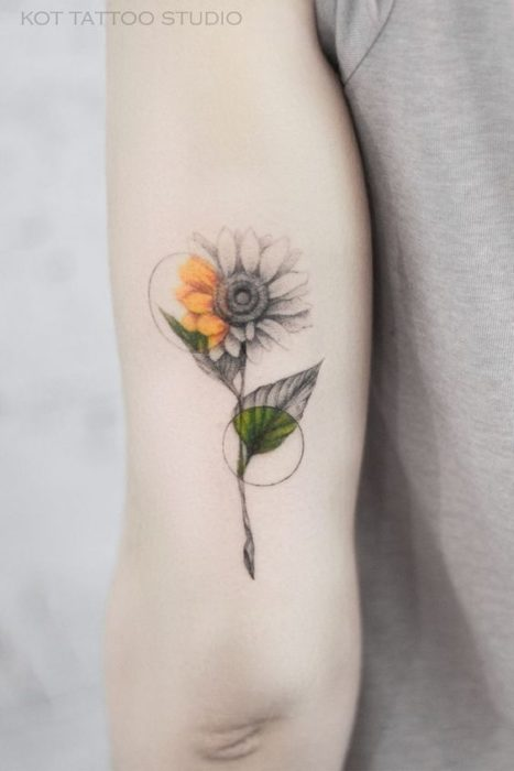Tattoo behind the arm of a sunflower in black and white with two circles that denote the sunflower's own colors