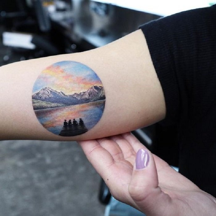 Tattoo on the inner part of the arm of a circle, showing a pier with some people sitting there looking at the sea