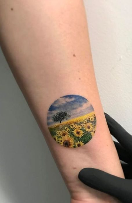 Tattoo on the wrist of a circle where a field of sunflowers appears