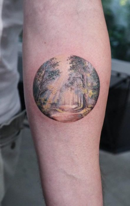 Tattoo on the inner part of the forearm of a path in the forest in soft colors