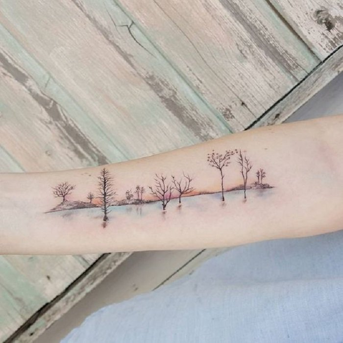 Tattoo in the area of ​​the forearm where you can see a part of the forest and the reflection of a lake in the lower part