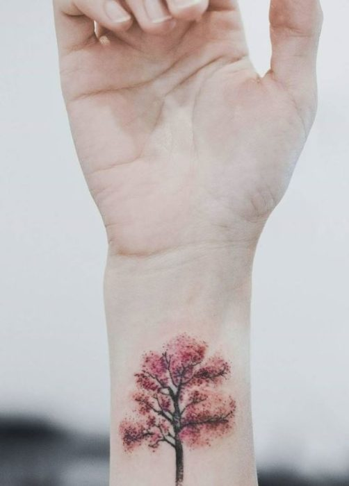 Tattoo on the wrist of a tree in autumn tones