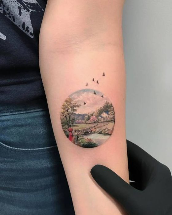 Tattoo on the forearm where is the landscape of a river and nature