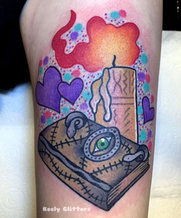 Tatuajes de la película de brujas Hocus Pocus; tatuaje de libro de hechizos y vela en la pierna