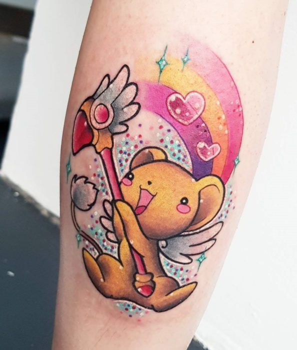 Sakura Card Captor tattoo with vivid colors, Kero with the seal key, rainbow and hearts, on the leg