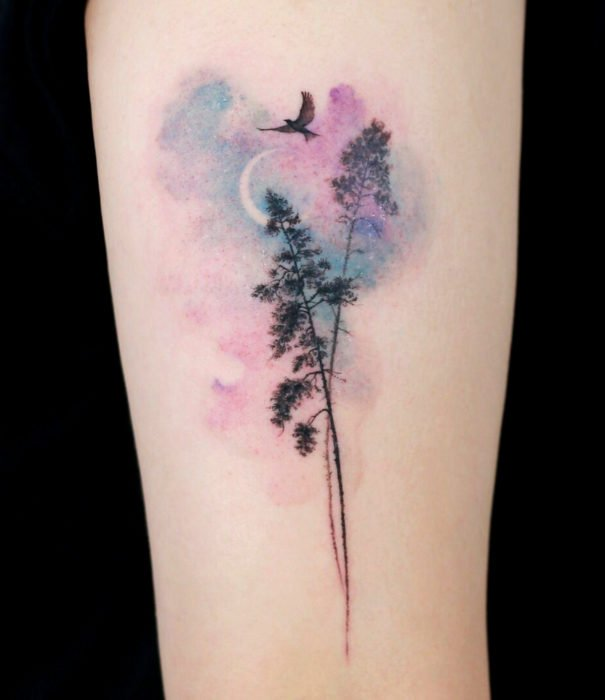 Pretty watercolor tattoo designs; Trees with universe in pastel background tattoo on arm