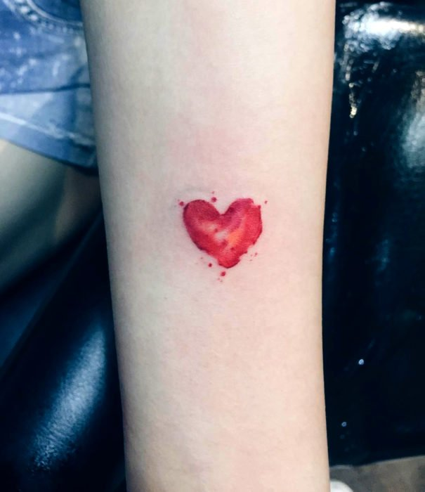 Pretty watercolor tattoo designs; Small red heart tattoo on arm