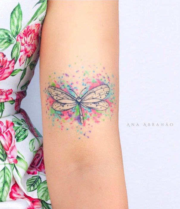 Pretty watercolor tattoo designs; Pastel dragonfly tattoo on arm