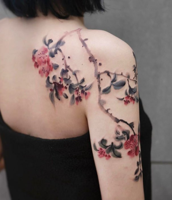 Pretty watercolor tattoo designs; flower tattoo on back, shoulder and arms