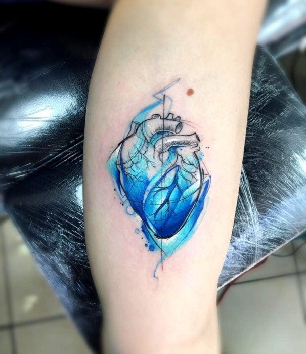 Pretty watercolor tattoo designs; Realistic blue heart tattoo on arm