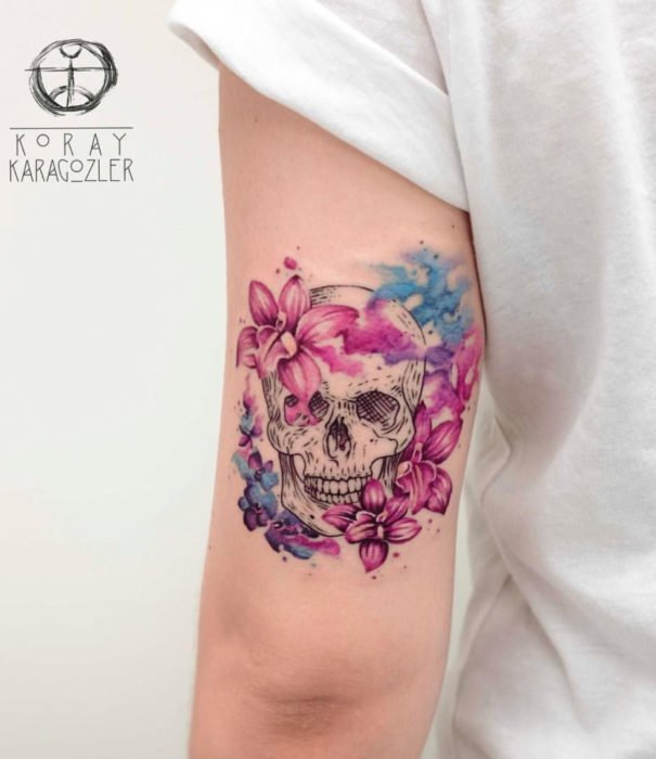 Pretty watercolor tattoo designs; Skull tattoo with flowers on the arm