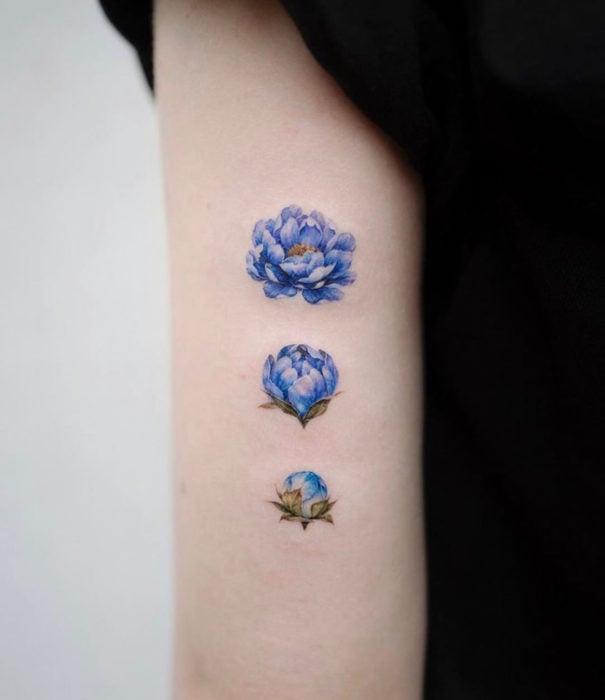 Pretty watercolor tattoo designs; Blue flower tattoo on arm