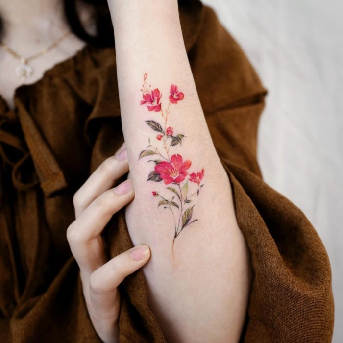 Tatuaje mini, pequeño de flores femeninas rojas en el antebrazo