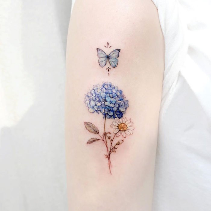 Mini, small tattoo of female flowers blue hydrangeas and white daisy with butterfly on the arm