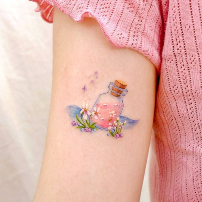 Mini tattoo, small of white female flowers with bottle with potion, on arm