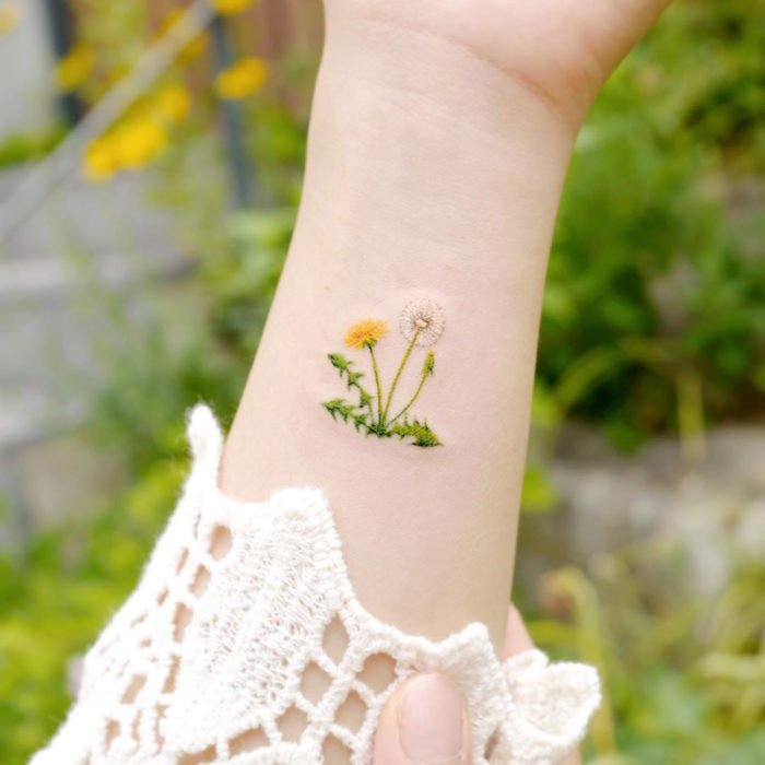 Mini, small tattoo of white and yellow female flowers, dandelions on the arm