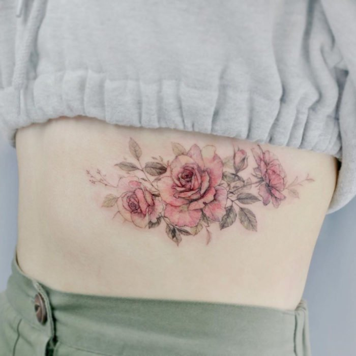 Mini tattoo, small of feminine pink flowers on ribs
