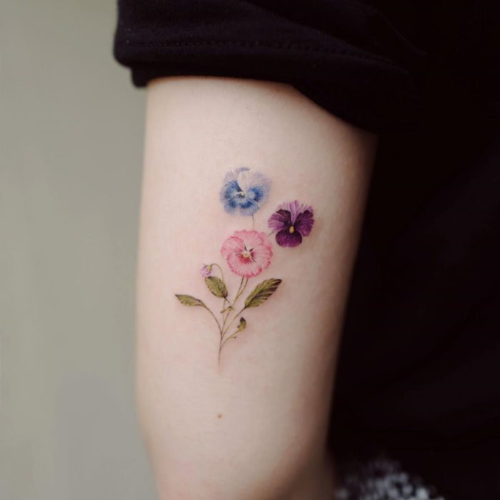 Mini, small tattoo of feminine flowers blue, pink and purple pansies on the arm, triceps