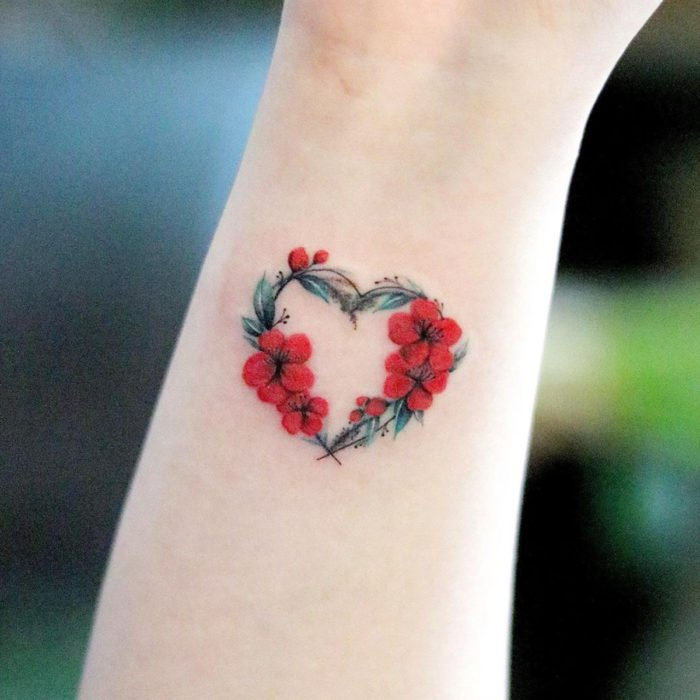 Mini, small tattoo of red female flowers forming a heart on the wrist