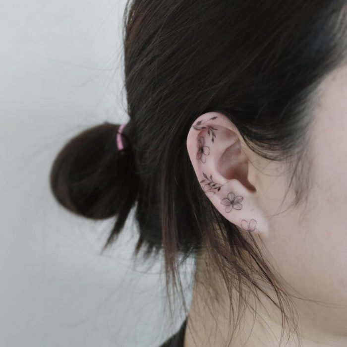 Mini, small tattoo of female flowers on the ear