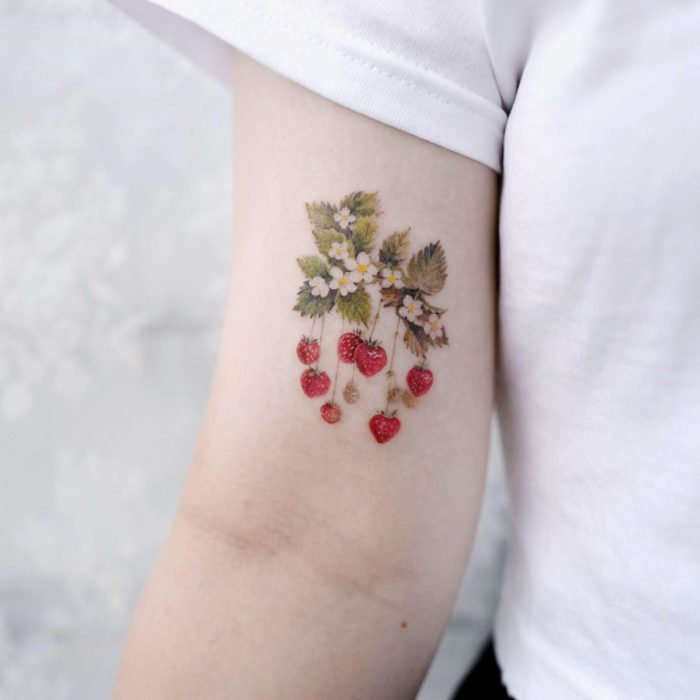 Mini tattoo, small of female flowers strawberries on arm, bicep