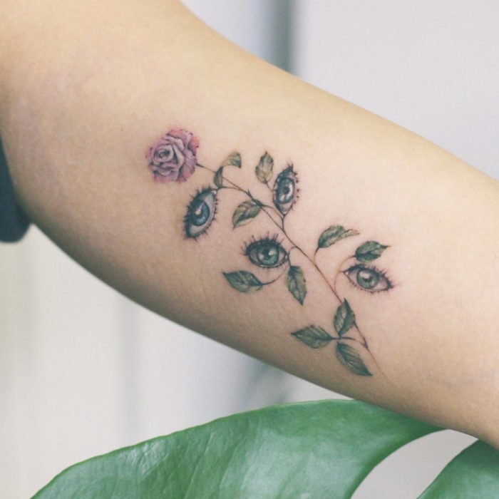 Mini tattoo, small of feminine pink flowers with eyes instead of leaves, on the arm