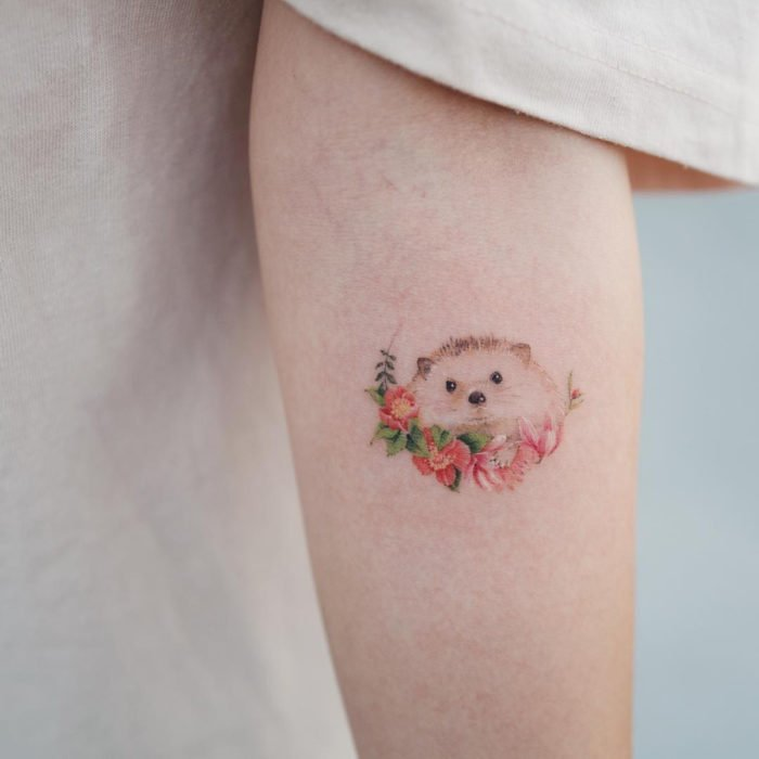 Mini tattoo, small of feminine pink flowers with hedgehog on the arm