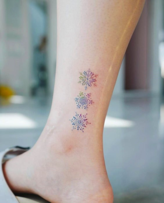 Tatuaje de copos de nieve en colores pastel en el tobillo