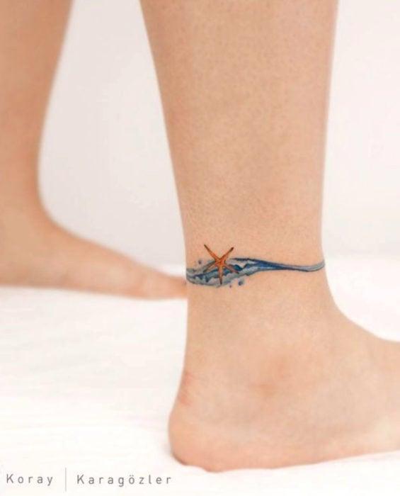 Tatuaje de ola y estrella de mar en el tobillo