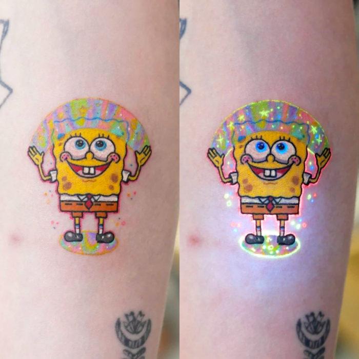 Tatuadora hace tatuajes bonitos, delicados y femeninos que brillan; tatuaje de Bob Esponja con arcoíris con destellos en el brazo