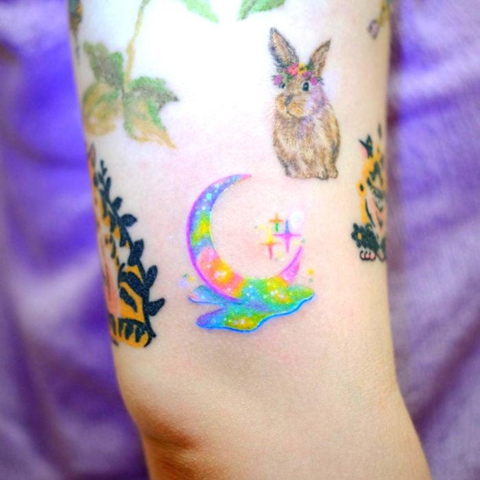 Tatuadora hace tatuajes bonitos, delicados y femeninos que brillan; tatuaje de media luna de colores morado, azul, rosa y verde pastel, conejo, en el brazo