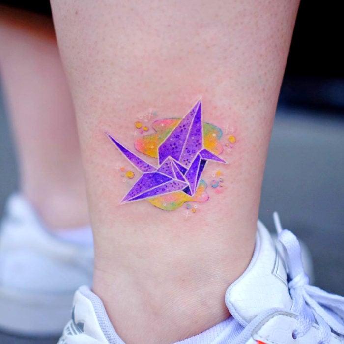 Tatuadora hace tatuajes bonitos, delicados y femeninos que brillan; tatuaje de grulla de origami color morado en el tobillo