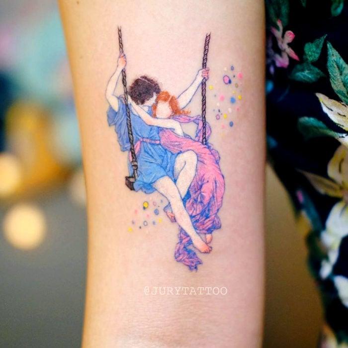 Tatuadora hace tatuajes bonitos, delicados y femeninos que brillan; tatuaje de pintura de Pierre Auguste Cot, La primavera, pareja en un columpio, minimalista en colores rosa y azul pastel en el brazo