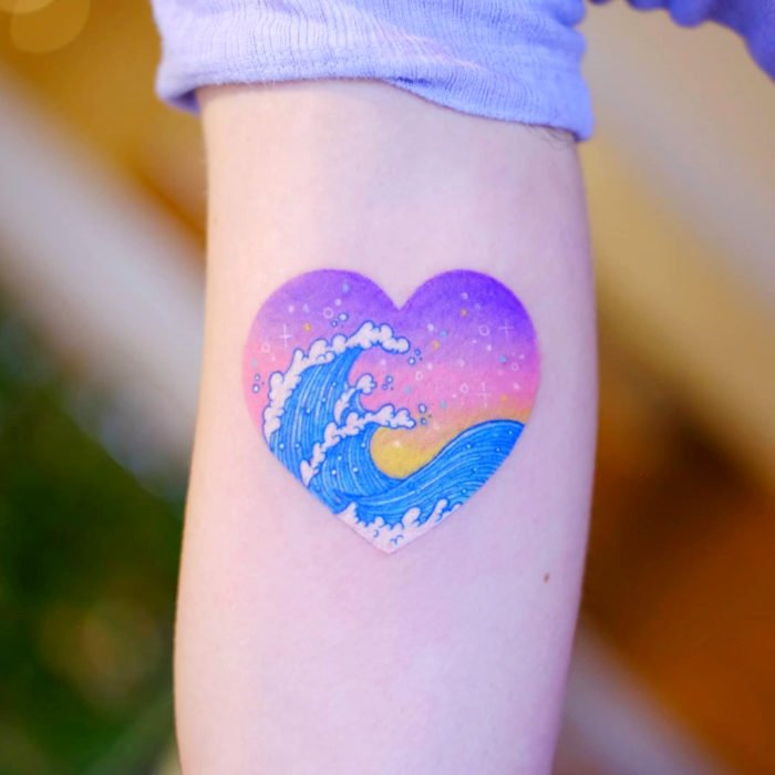 Tatuadora hace tatuajes bonitos, delicados y femeninos que brillan; tatuaje de ola japonesa dentro de corazón color morado, rosa, amarillo y azul pastel