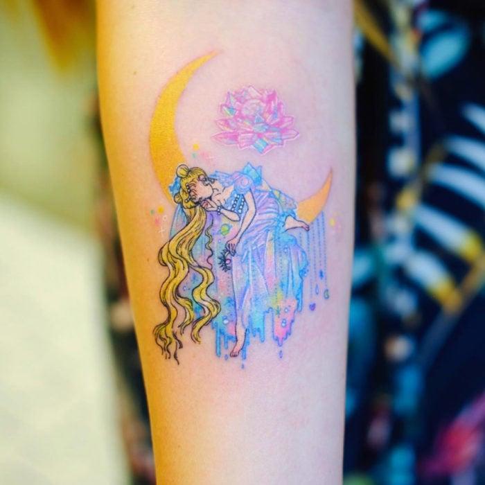 Tatuadora hace tatuajes bonitos, delicados y femeninos que brillan; tatuaje de Sailor Moon, Reina Serenity en la luna con vestido de colores rosa, morado y azul pastel